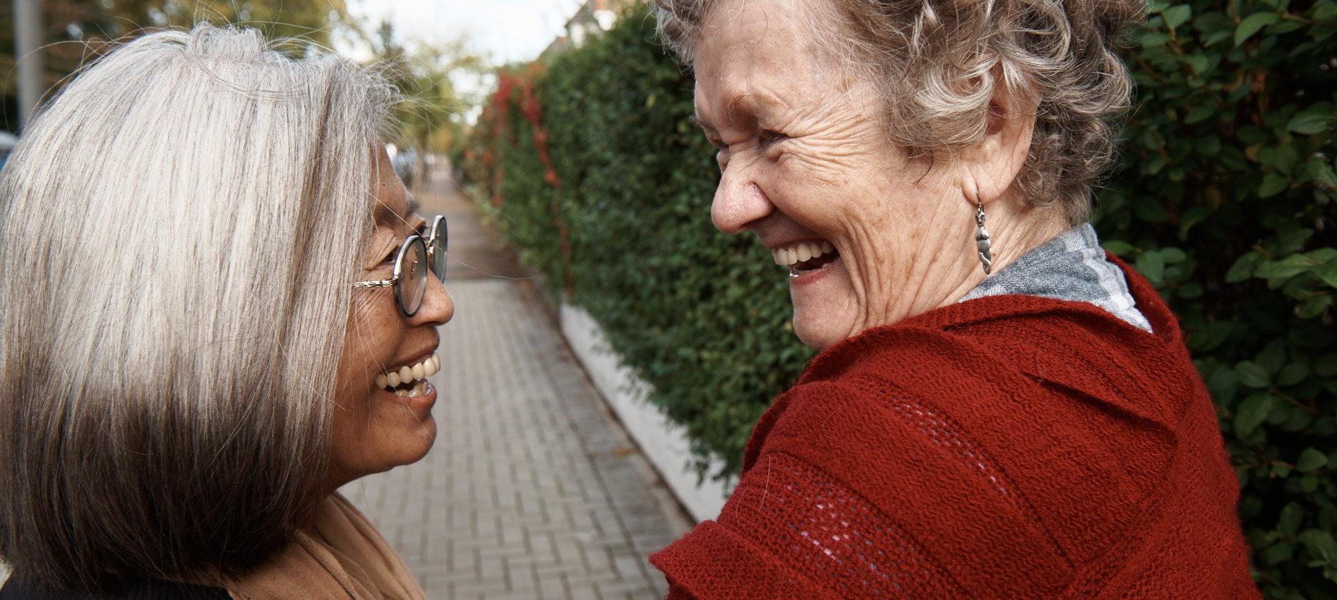 guild living two older friends walking outside smiling